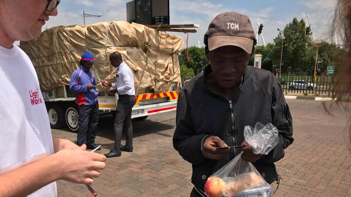 Homeless man receiving food parcels from Mormon members