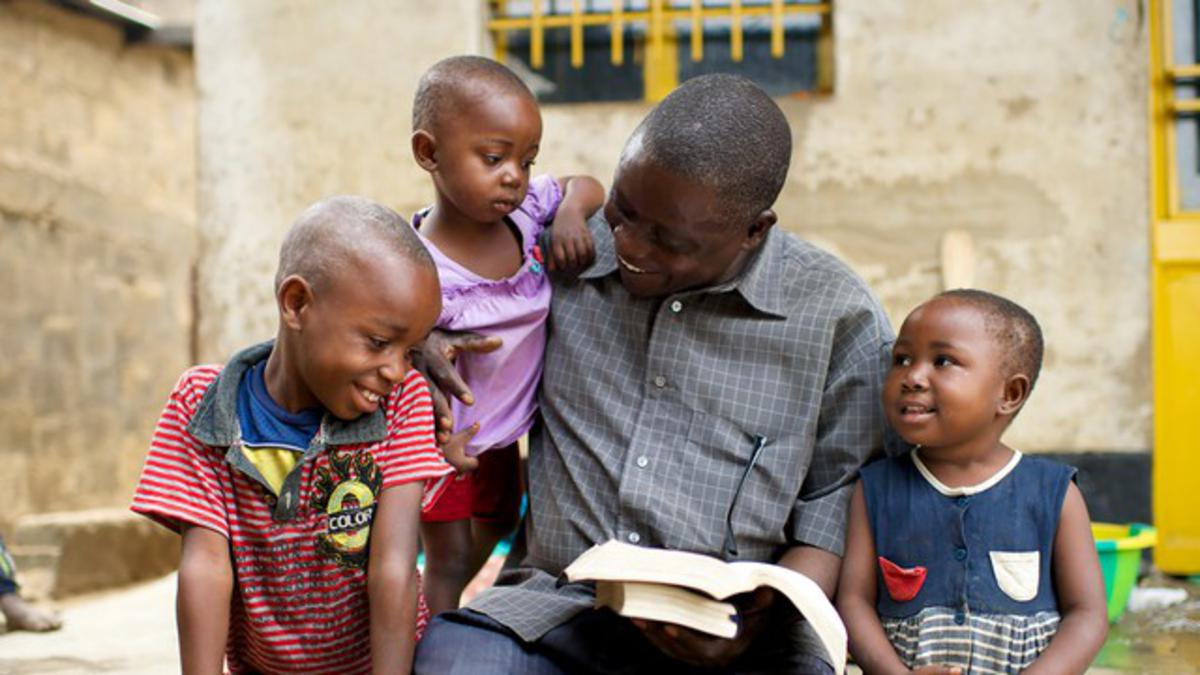 Mormon father reading scriptures with his children