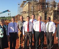 Elder Ronald A. Rasband, center, and other Church leaders stand outside the construction site of the future Durban South Africa Temple.