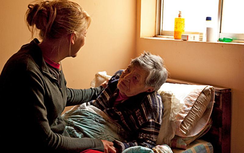 Una mujer conversa junto al lecho de una anciana enferma