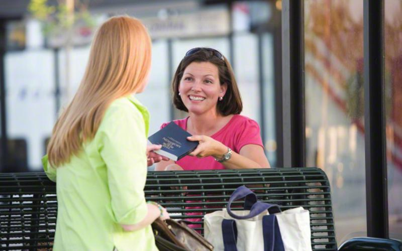 Woman giving away book of mormon