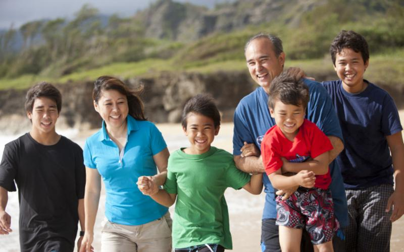 A family in Hawaii walks along the beach together