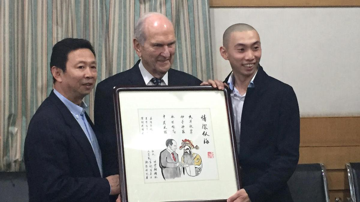 President Nelson receives a painting from the son and grandson of the late Chinese opera star, Fang Rongxiang, at Shandong University School of Medicine in Jinan, China.