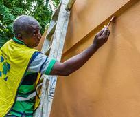 Hombre pintando un edificio en el día internacional de servicio