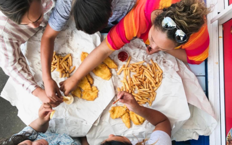 Youth from New Zealand share a feed of fish 'n chips