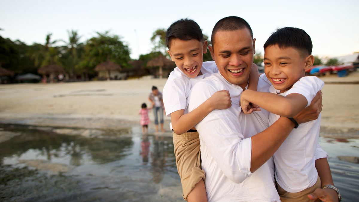 A father playing with his sons by the beach