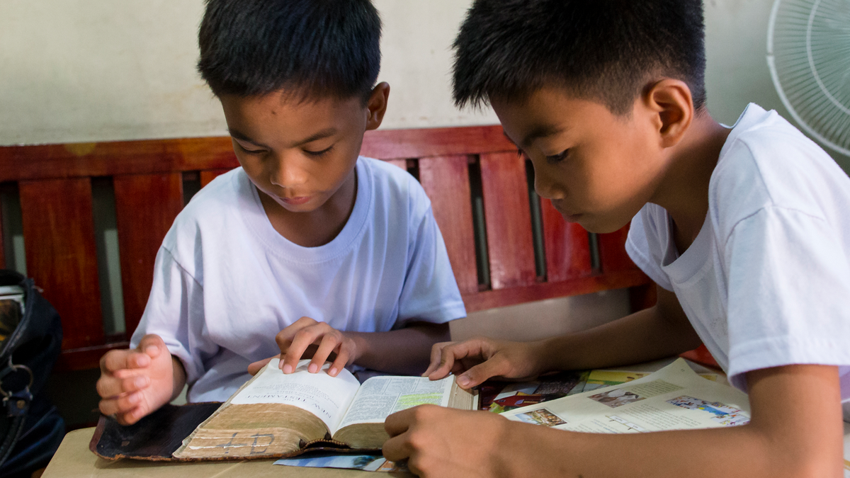 Two young men studying the scriptures.