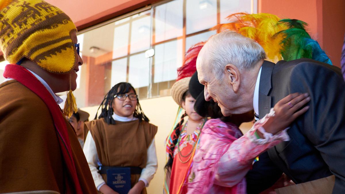 El Presidente Russell M. Nelson y su esposa Wendy son saludados por niños bolivianos