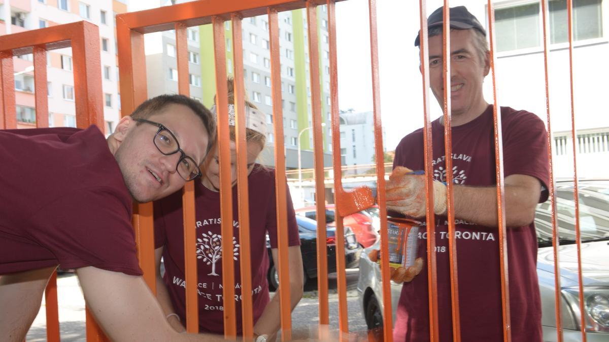 Dobrovoľníci pri natieraní plota