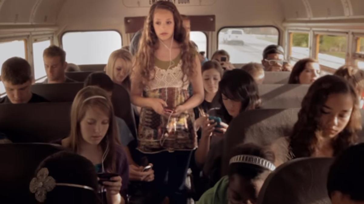 Una joven escucha música en un autobús lleno de jóvenesusando sus celulares