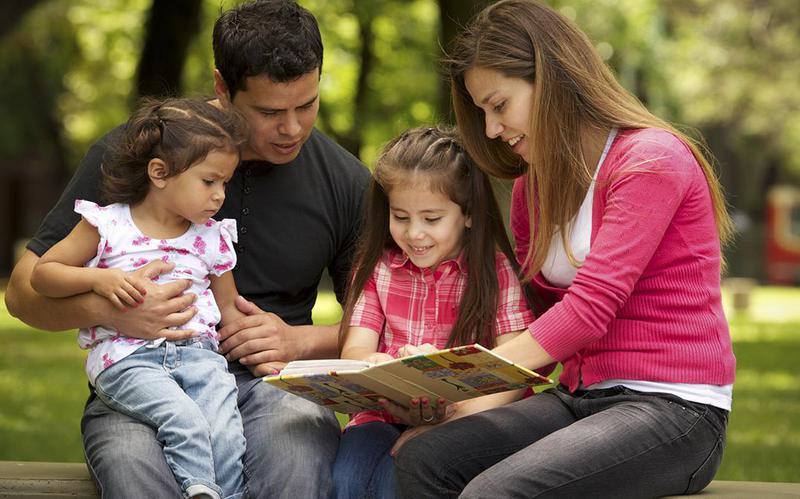 Papá y mamá leen un cuento a sus hijas en el parque