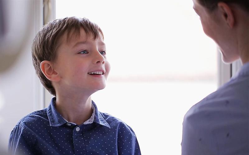 Un niño mira sonriente a su padre.