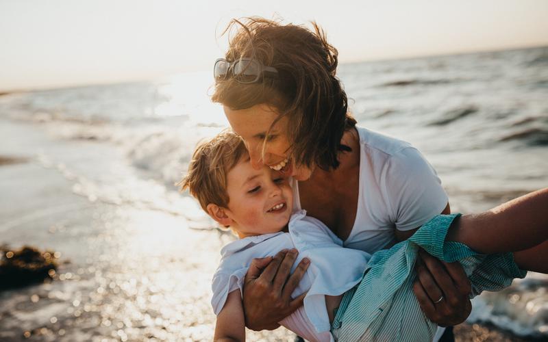 Naerusuised ema ja laps rannas