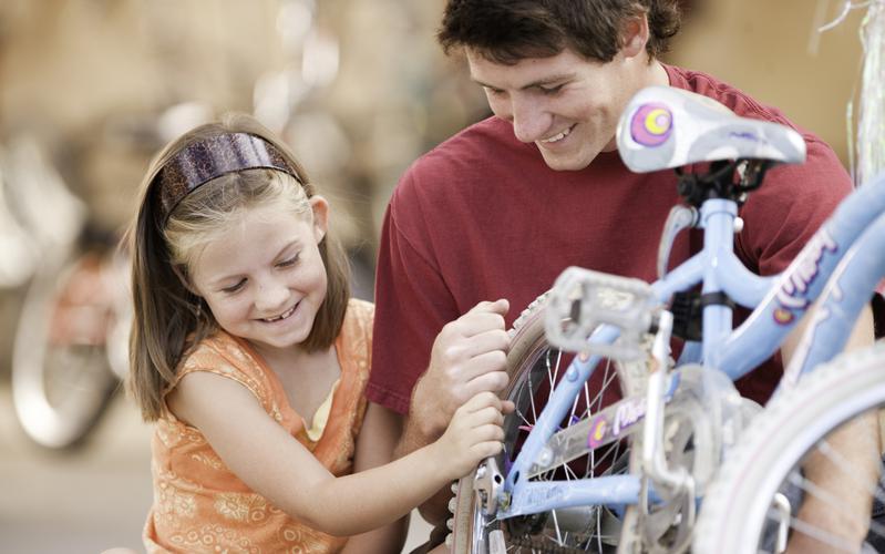 Mees parandab koos tüdrukuga ratast