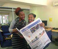 Sisters looking in the newspaper for jobs