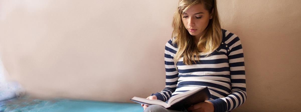 Jovem Santo dos Últimos Dias lendo o livro de Mormon. Tanto a Bíblia quanto o Livro de Mórmon testemunham sobre Jesus Cristo.