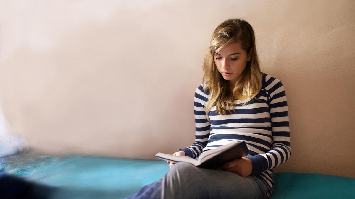 Jovem membro de A igreja de Jesus Cristo dos Santos dos Últimos Dias lendo o livro de Mormon. Tanto a Bíblia quanto o Livro de Mórmon testemunham sobre Jesus Cristo.