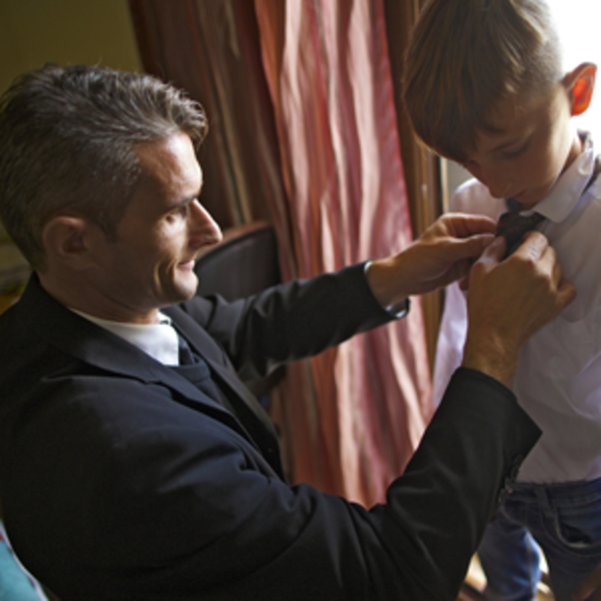 Father helping his son get ready for church