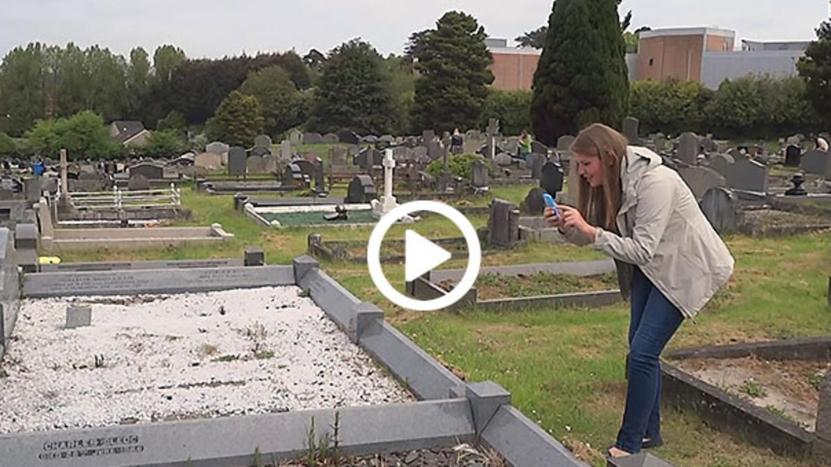 girl documenting grave stones
