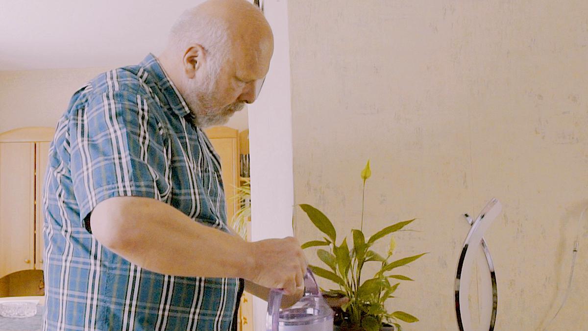 Ein Mann gießt eine Pflanze
