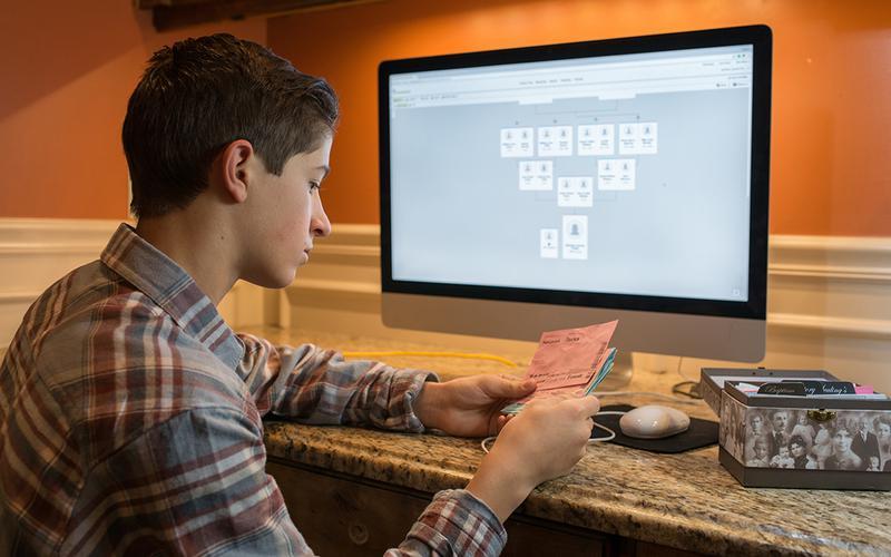 Ung mand sidder med kort med navne på forfædre med FamilySearch i baggrunden