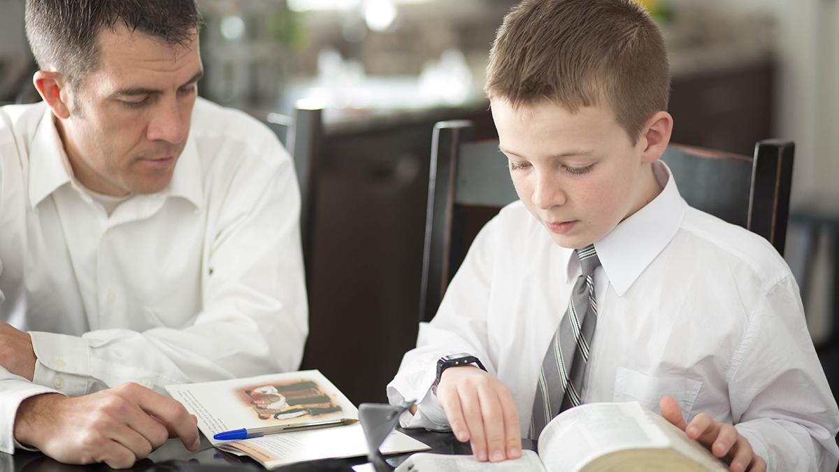 Tată studiind scripturile împreună cu fiul