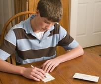 Ein junger Mann füllt einen Zehtenzettel aus.