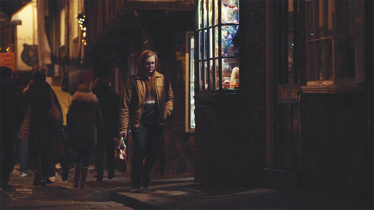 En ung man går längs gatan på kvällen runt jultiden.