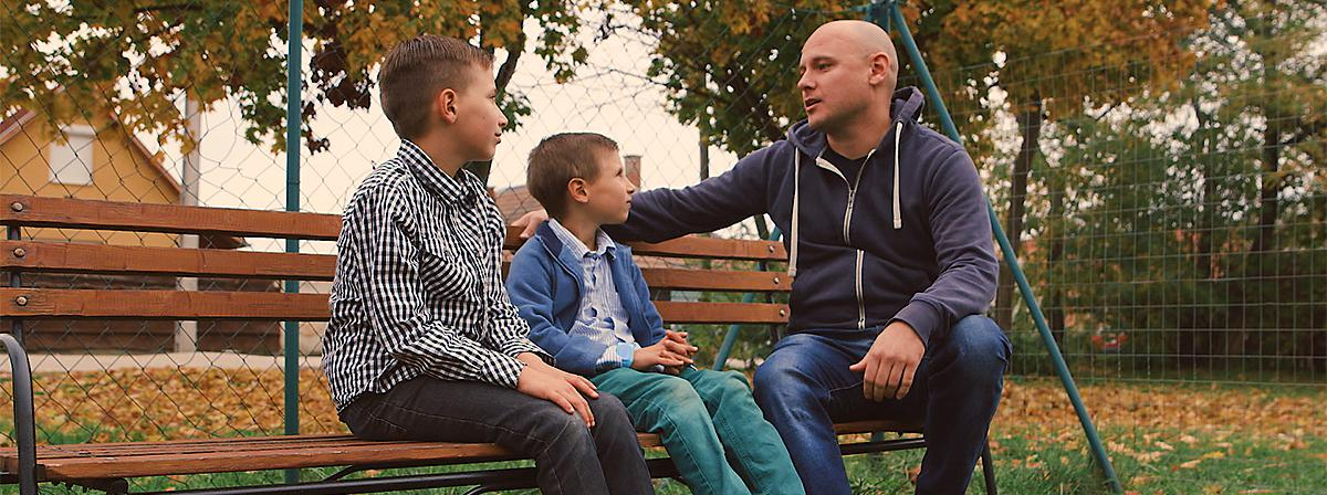 a father with two sons on a bench
