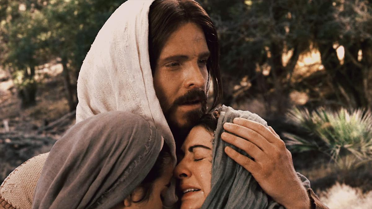 Jesus Kristus omfamnar en gråtande kvinna.