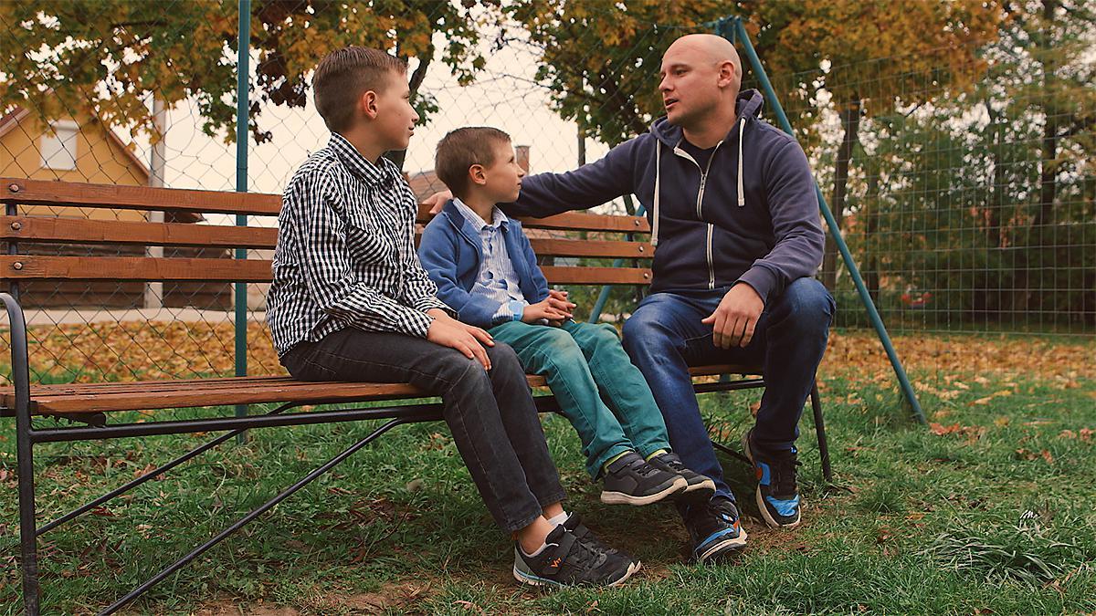 ein Vater sitzt mit zwei Söhnen auf einer Bank