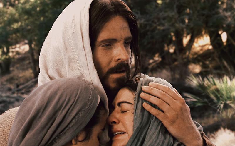 Gesù Cristo abbraccia una donna che piange.