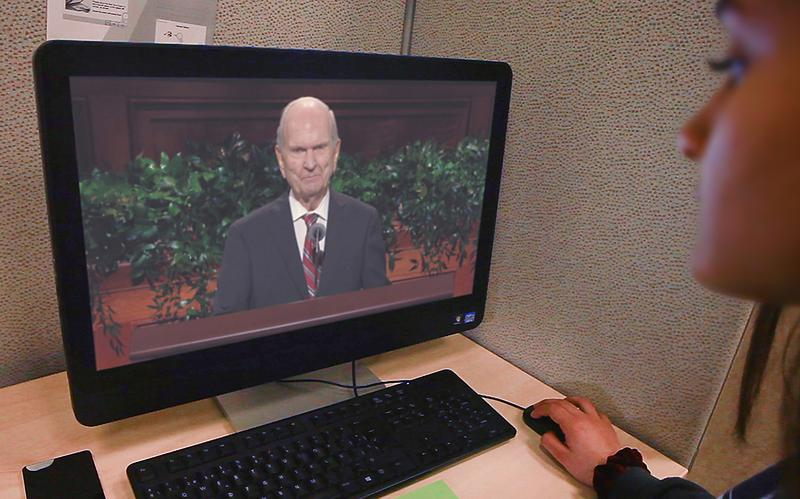 a girl watching general conference on a computer