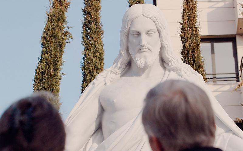 Para patrząca na rzeźbę przedstawiającą Chrystusa.