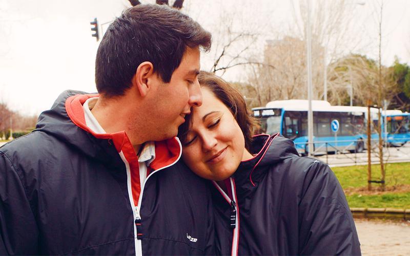 Um casal jovem e sorridente a abraçar-se.