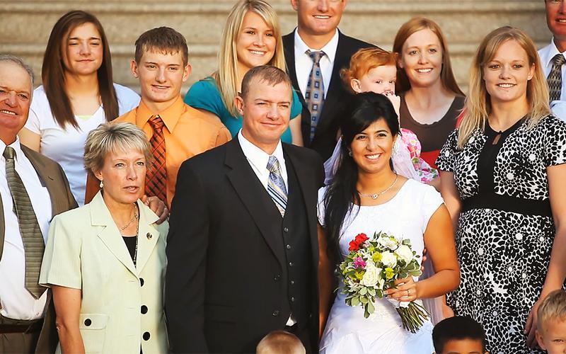 Onnellinen perhe koolla hääjuhlassa.
