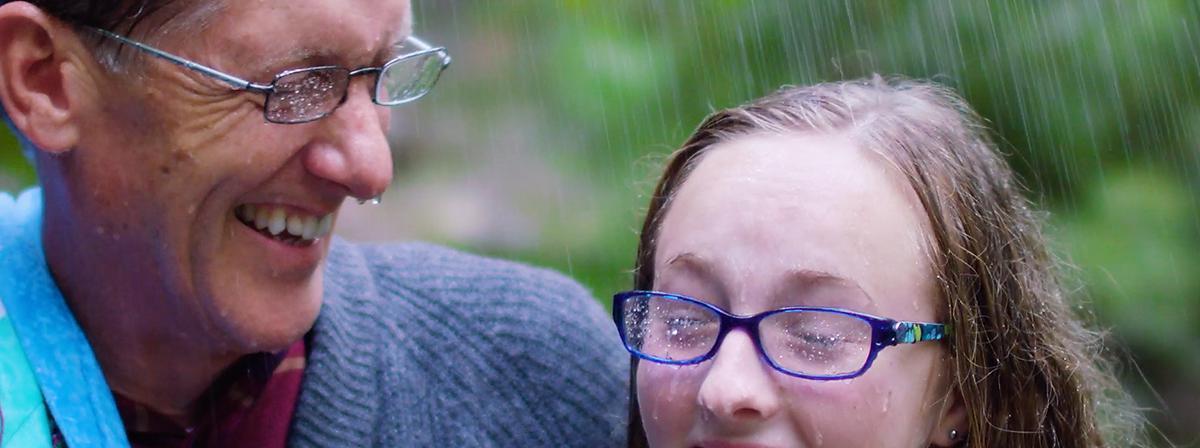 Čovjek i njegova unuka smiju se zajedno na kiši.