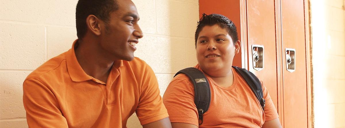 Dois rapazes demonstram ser amigos no corredor da escola.