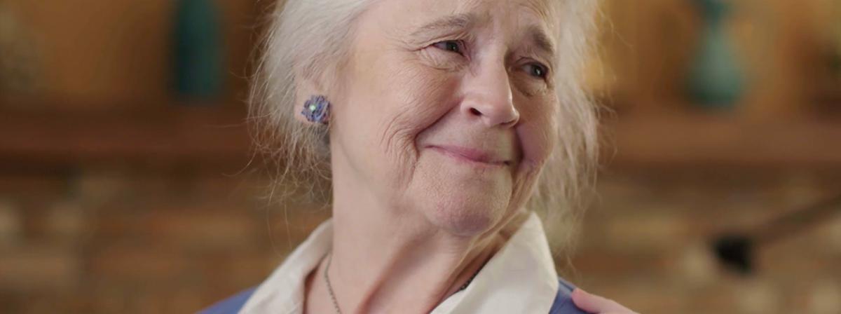 Starsza kobieta uśmiecha się, kiedy czuje dotyk dłoni na swoim ramieniu