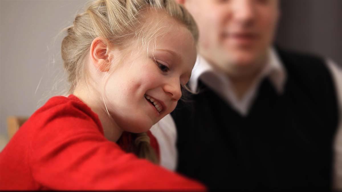 Hymyilevä, nuori tyttö pelaamassa korttia perheensä kanssa.