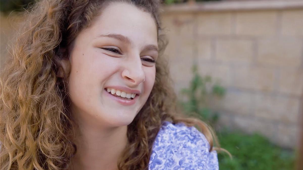 Hymyilevä, nuori tyttö nauramassa.
