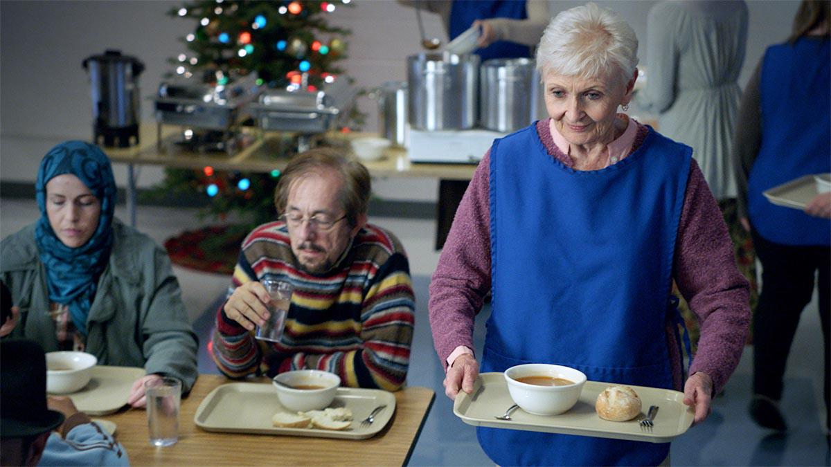 Vanha nainen jakamassa ruokaa vapaaehtoisena.