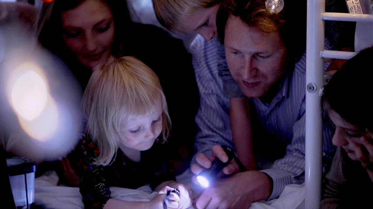 Eine Familie liest mit einer Taschenlampe unter der Decke ein Buch.