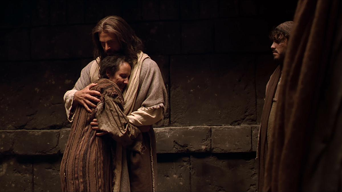 Jesus omfamnar en man.