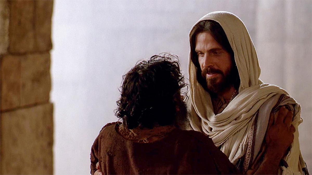 Le Christ relève un homme qui est tombé.