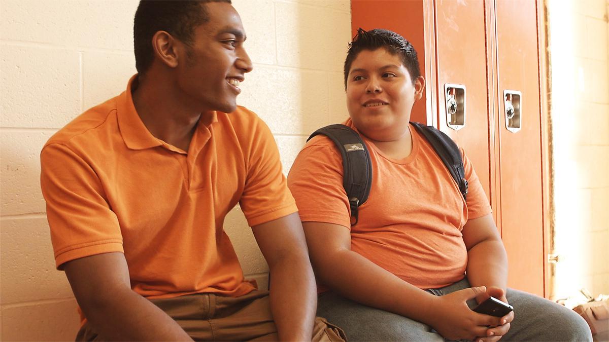 Két fiú barátkozik az iskola folyosóján