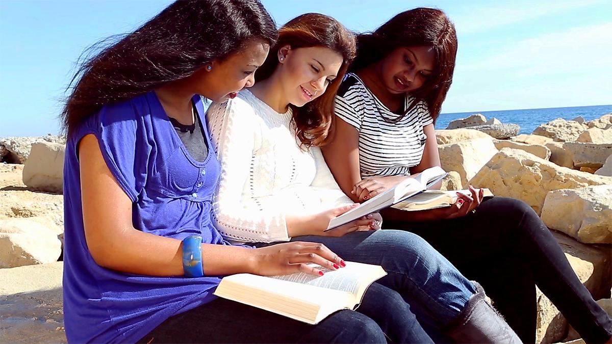 Trois filles assises au bord de la mer, lisent les Écritures.
