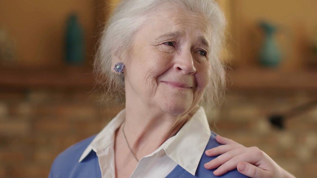 O femeie în vârstă zâmbește în timp ce cineva pune mâna pe umărul ei.