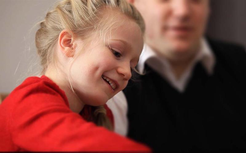 Smilende, ung pike som spiller kort med sin familie.