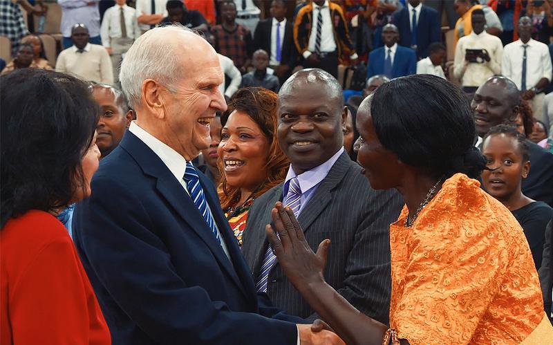 O profeta cumprimenta e sorri para uma mulher da Igreja.